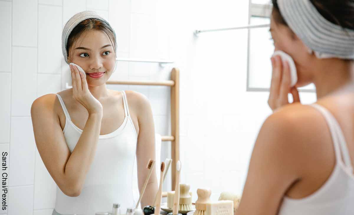 Foto de una mujer limpiando su rostro con un pomo que ilustra para qué sirve la vitamina E en la cara