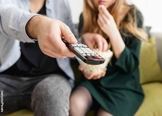 Foto de una persona cambiando de canal con el control remoto