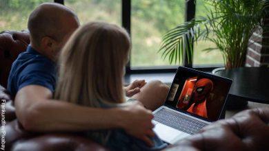 Foto de una pareja sentada viendo el computador que revela las películas para ver en pareja