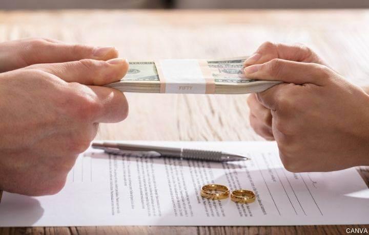 Foto de un par de manos jalando billetes en divorcio