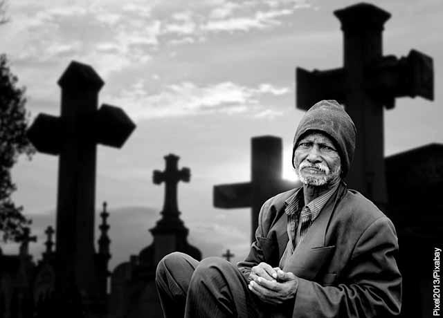 Foto de un anciano sentado en un cementerio