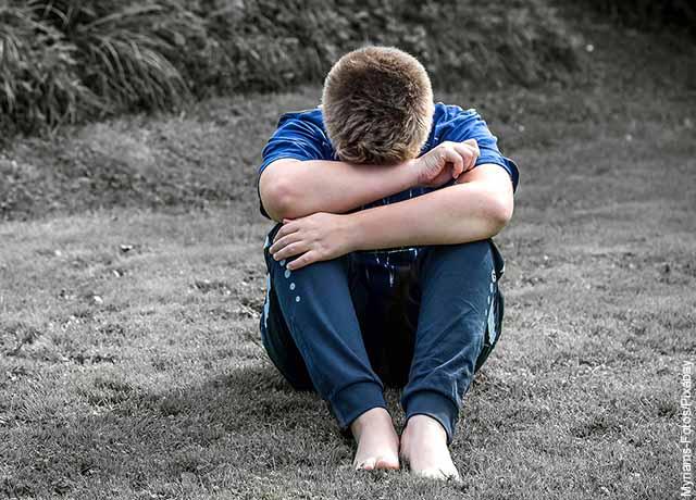 Foto de un joven sentado llorando que muestra qué significa soñar que alguien se muere pero está vivo