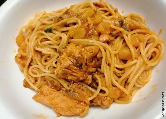 Foto de plato de espagueti con trozos de pollo y maíz