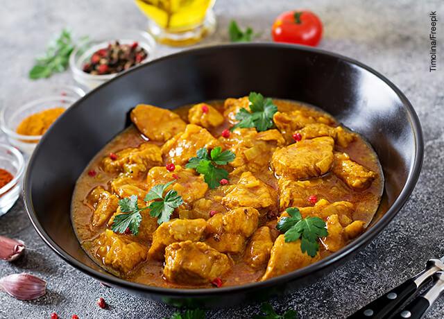 Foto de un bol negro lleno de curry y pollo