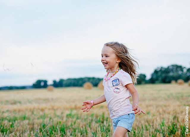Foto de una niña corriendo por el campo