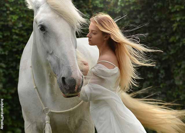 Foto de una mujer consintiendo un caballo
