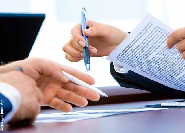Foto de una persona firmando un contrato que muestra lo que significa soñar con trabajo