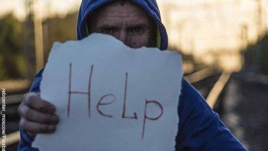 Foto de una persona sosteniendo un letrero de ayuda que muestra lo que es soñar que me disparan