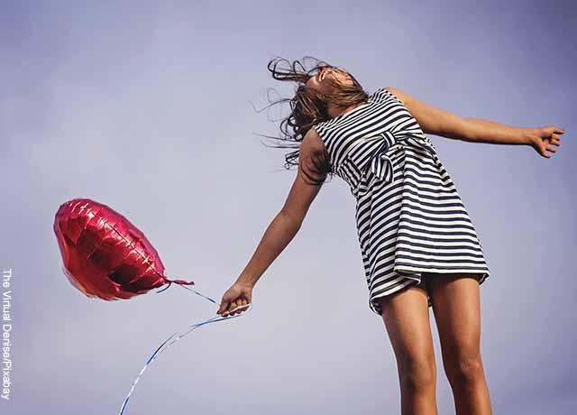 Foto de una mujer feliz con un globo de corazón en su mano