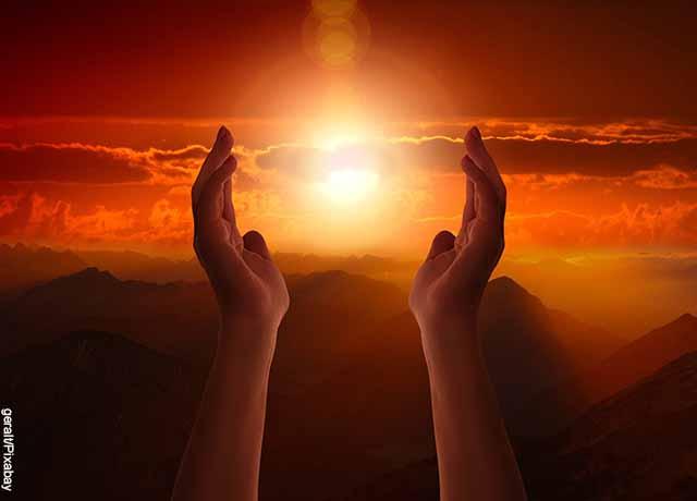 Foto de dos manos elevados al cielo