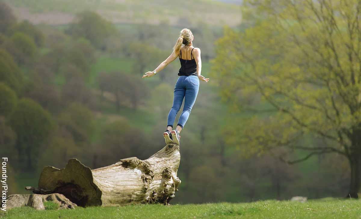 Foto de una mujer haciendo equilibrio sobre un tronco que muestra el 4444 y su significado espiritual