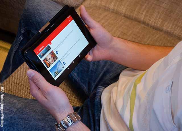 Foto de un hombre sentado viendo su tablet