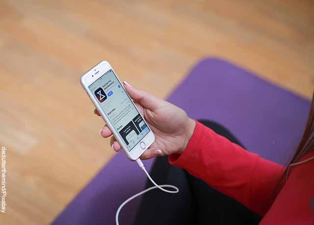 Foto de una mujer viendo la pantalla de su teléfono