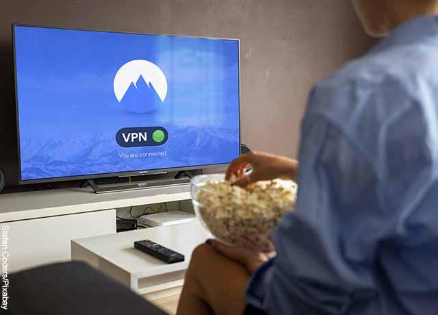 Foto de un hombre comiendo maíz y viendo su tv