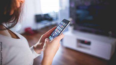 Foto de una mujer sosteniendo su celular en las manos que muestra las aplicaciones para ver películas gratis