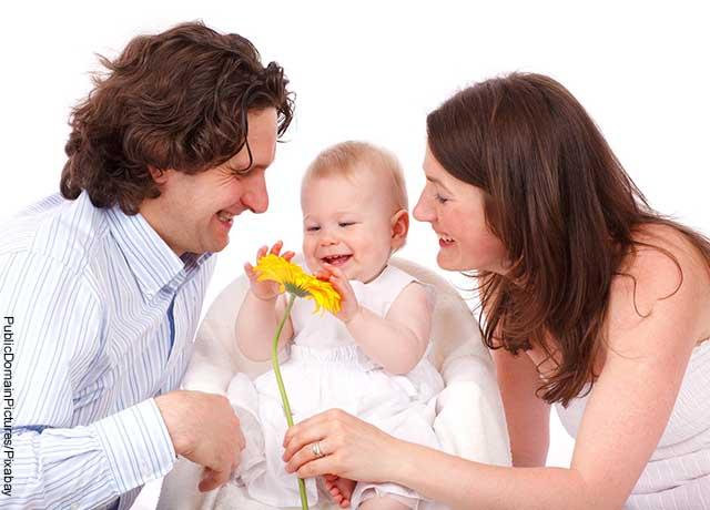 Foto de padres jugando con su hija con una flor