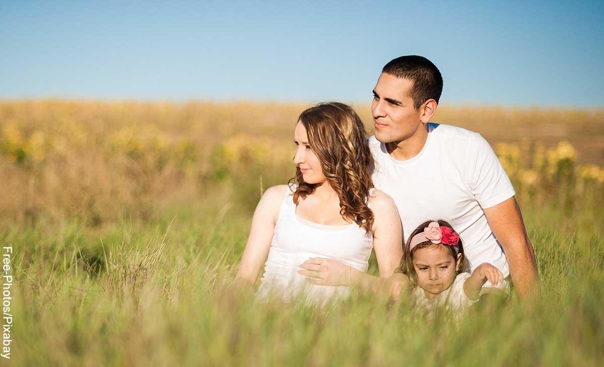 Foto de padres con su hija sentados en el campo que revela las canciones para dedicar a un hijo