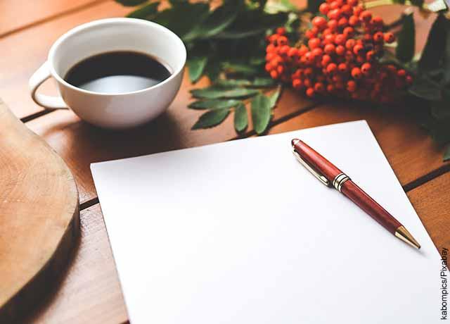 Foto de una libreta con un esfero y una taza de café sobre una mesa