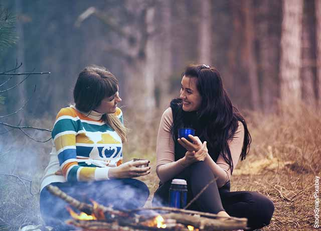 Foto de dos mujeres tomado té y hablando en un parque que revela cómo cuidar la salud mental