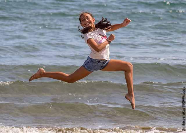 Foto de una niña saltando sobre la arena