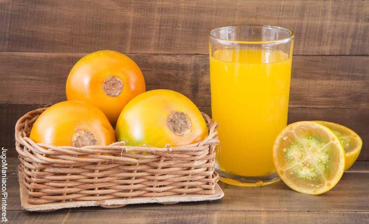 Foto de un jugo junto con frutas tropicales que revelan cómo hacer jugo de lulo