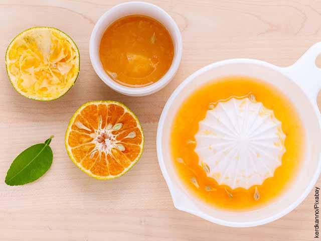 Foto de un jugo de mandarina sobre una mesa de madera