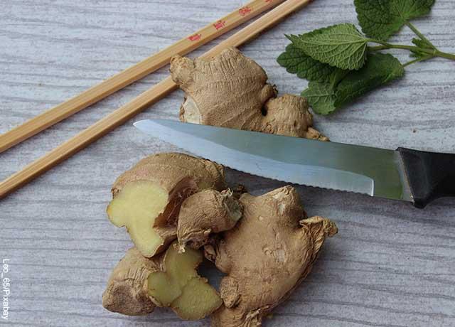Foto de un cuchillo con trozos de jengibre sobre una mesa