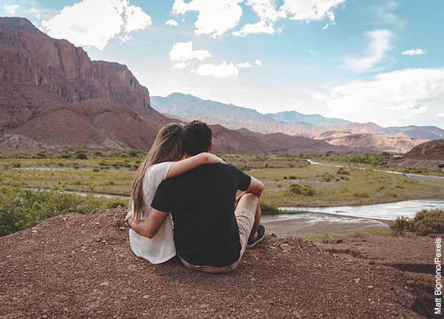 Foto de una pareja abrazada mirando la naturaleza