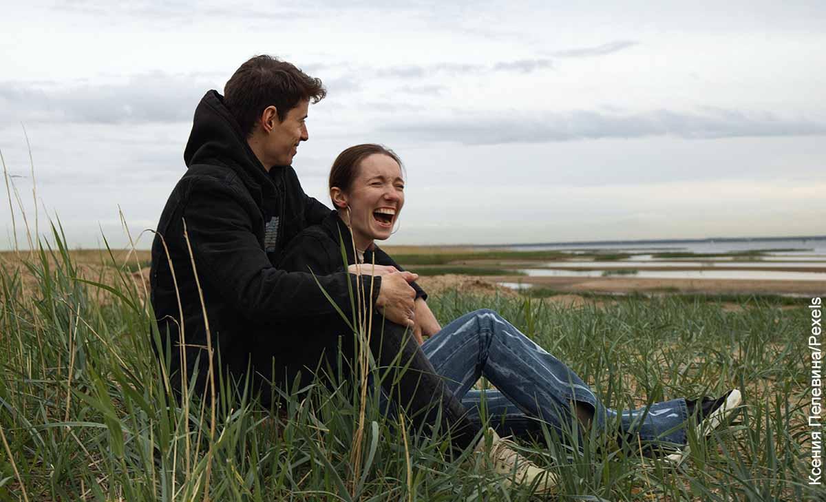 Foto de una pareja riendo sentada en un paisaje que revela las cosas para hacer en pareja