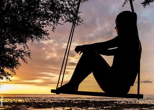 Foto de una mujer sentada en un columpio en la playa