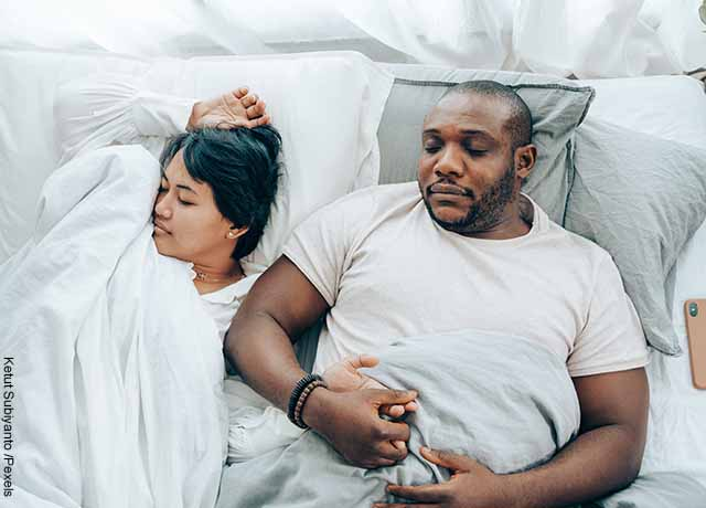 Foto de una pareja durmiendo en su cama