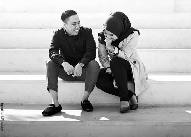 Foto de un hombre y una mujer riendo en unas escaleras