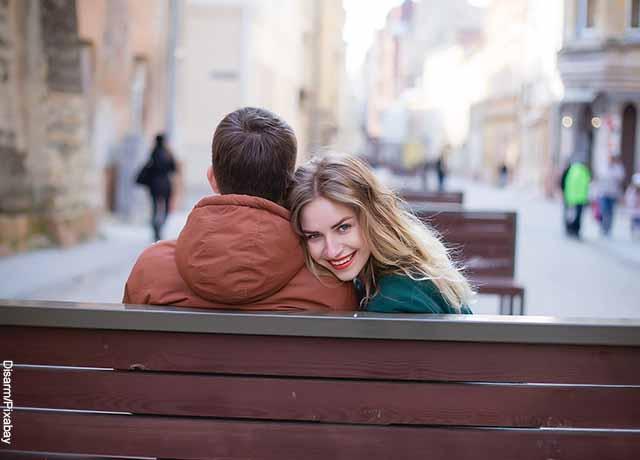 Foto de una mujer riendo sentada con un hombre en una banca