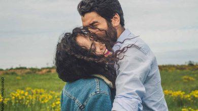 Foto de novios felices en un campo que muestra preguntas para conocer a tu pareja
