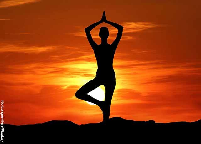 Foto de la sombra de una persona haciendo yoga al atardecer
