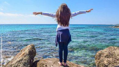 Foto de una niña parada sobre una roca frente al mar que revela qué es la dimensión espiritual