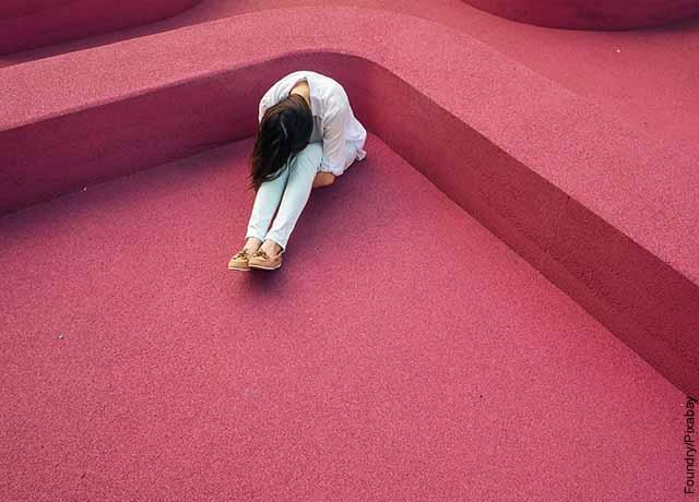 Foto de una persona sentada en un tapete rosado