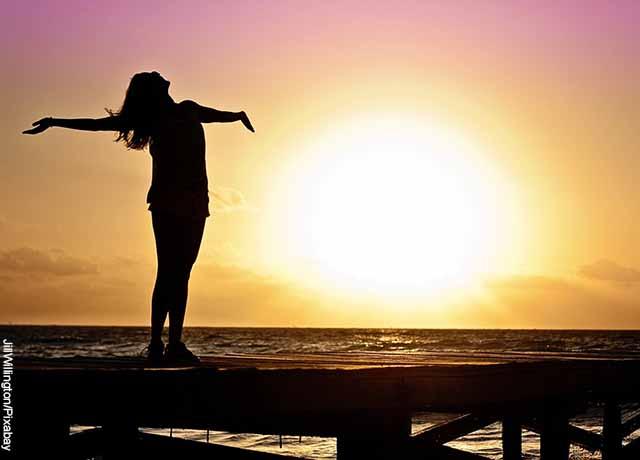 Foto de una joven con los brazos abiertos frente al mar