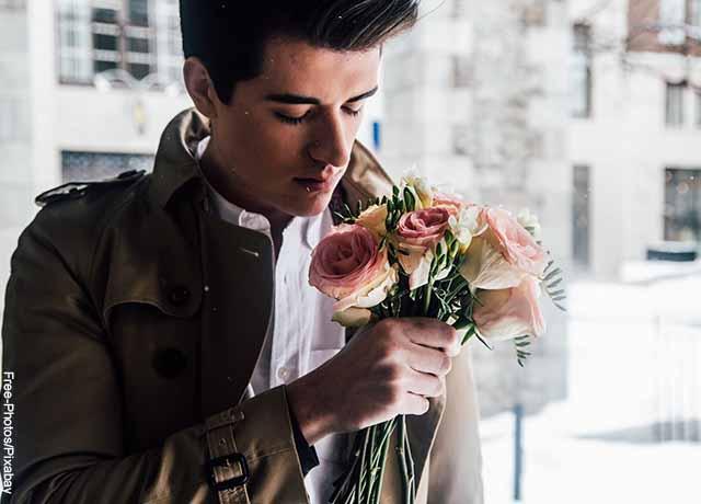 Foto de un hombre con unas rosas en la mano que muestra qué significa el signo Sagitario