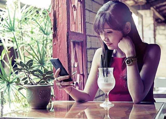 Foto de una mujer viendo su celular que muestra qué significa TBT
