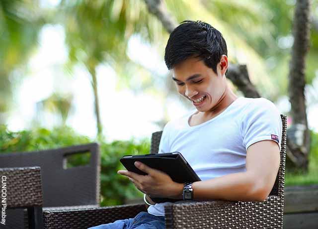 Foto de un hombre mirando una tablet y riendo