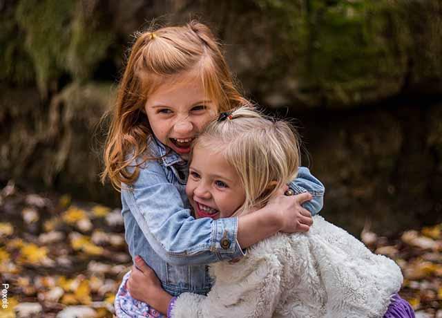 Foto de dos niñas abrazadas sonriendo