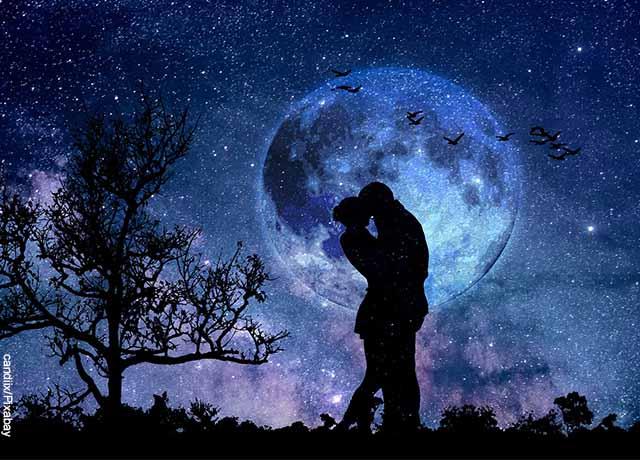 Foto de dos personas besándose en la noche bajo las estrellas