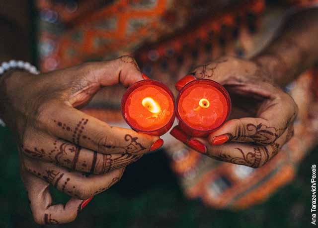 Foto de una mujer sosteniendo dos velas rojas