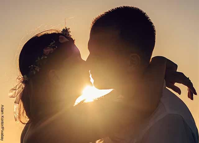 Foto de una pareja besándose al atardecer