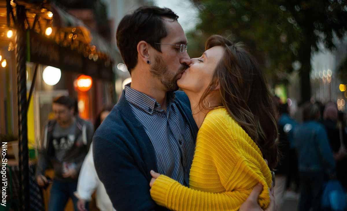 Foto de una pareja besándose en la calle que revela el significado de los besos
