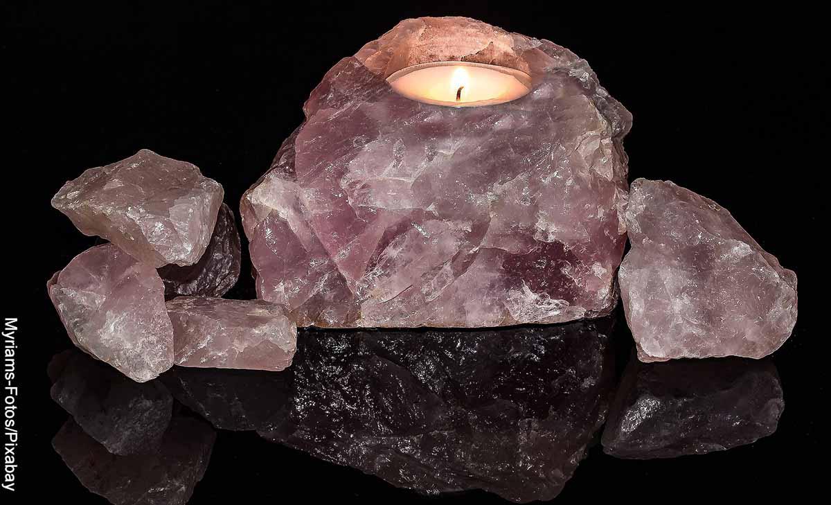 Foto de una piedra mineral rosada con una vela que muestra el significado de los cuarzos