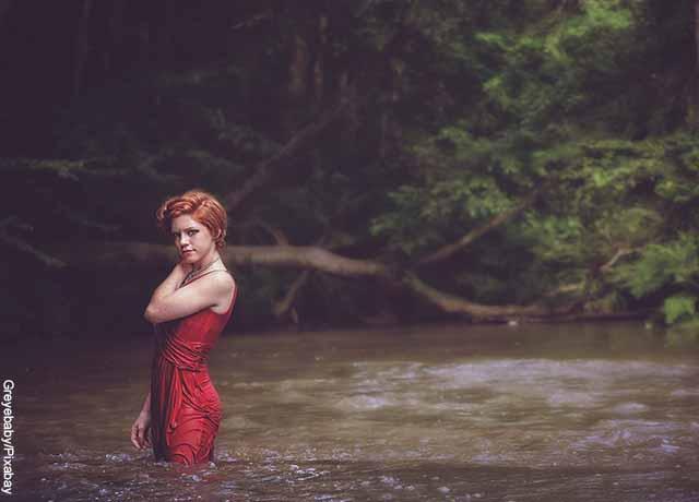 Foto d euna mujer metida en un río con un vestido rojo