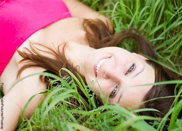 Foto de una mujer acostada sobre el pasto que muestra el significado de nombres de mujer