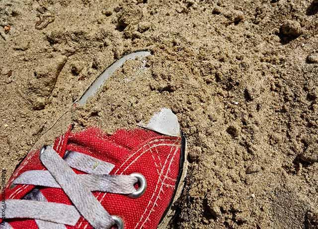 Foto de un zapato enterrado que revela lo que es soñar con arena